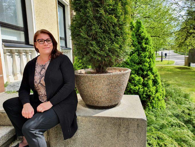 Koordinaattori Anette Lehtonen istuu kaupungintalon edustalla.