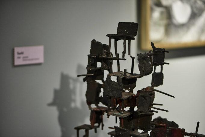 Kuvassa on Ossi Somman pronssiveistos nimeltä Tuolit, taustalla näkyy seinällä olevasta teoksesta vain alakulma