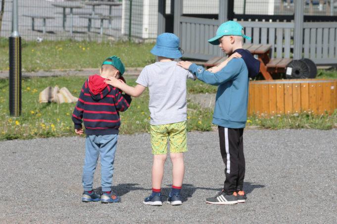 Kolme päiväkoti-ikäistä poikaa seisoo pihalla selät kohden kameraa ja pitävät toisistaan kiinni.