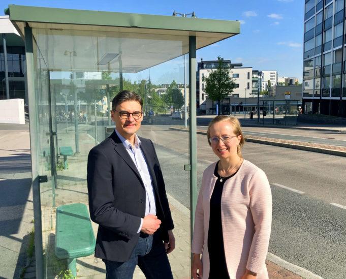 Kaupunkikehitysjohtaja Mikko Nieminen ja logistiikkainsinööri Milla Valkonen seisovat Nokian keskustassa bussipysäkillä aurinkoisena kesäpäivänä.