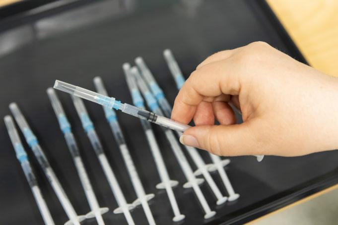 Kuvassa on pöydällä koronarokotteita ja hoitajan kädessä yksi rokote.