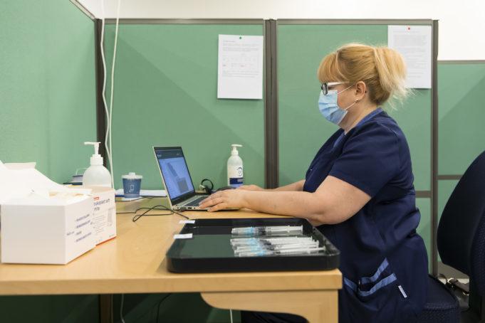 Kuvassa hoitaja istuu tietokoneen äärellä Nokian koronarokotuspisteellä.