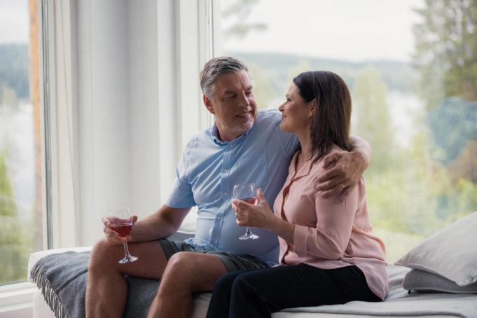 Vanhempi pariskunta halaa toisiaan sohvalla ja taustalla näkyy järvimaisema omakotitalon ikkunasta.