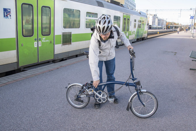 Mies kasaa taittopyörää asemalaiturilla.
