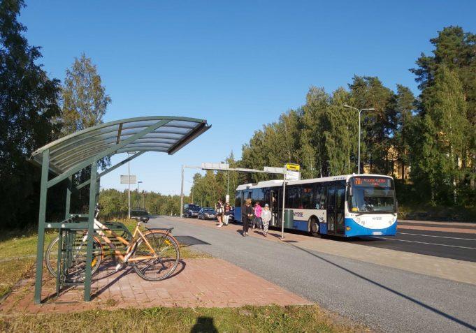 Aikuisia ja lapsia nousee pois bussine kyydistä Nokianvaltatien pysäkillä, jonka edessä on myös pyöräkatos polkupyörille.