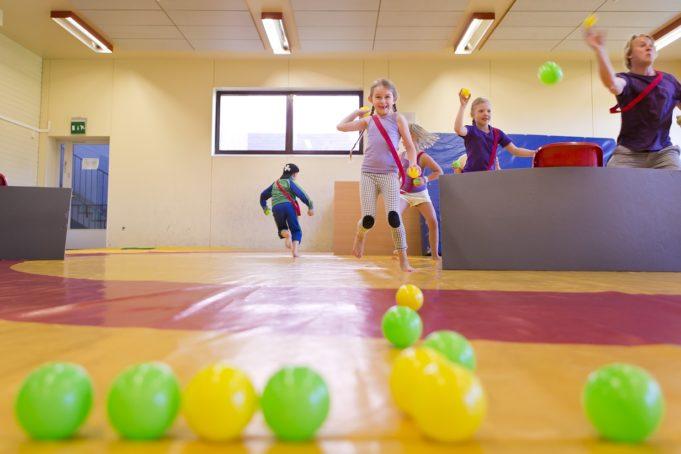 lapset leikkii palloilla