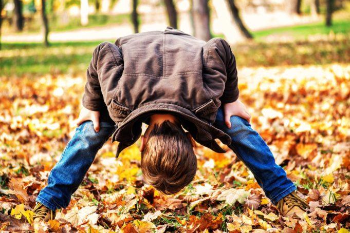Poika kurkistaa jalkojen välistä syksyn lehtiä